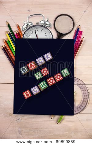 Back to school message against students desk with black page