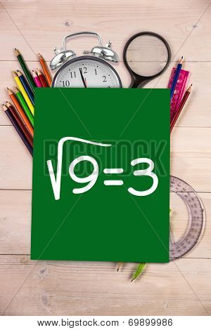 Square root of three against students desk with green page