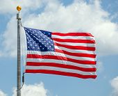 foto of flag pole  - The American flag waving against a blue sky on a flag pole focus on star of waving flag