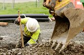 picture of excavator  - Worker using a small tracked excavator to dig a hole to fix a water leak at a large commercial housing development in Oregon - JPG