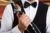 stock photo of waiter  - Portrait of a waiter holding a champagne bottle - JPG