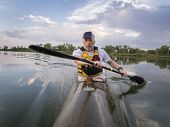 stock photo of collins  - senior male is  paddling racing sea kayak  on a calm lake with storm clouds in background - JPG