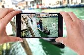 stock photo of gondolier  - a mobile phone snapping a picture of a gondolier on his gondola in venice - JPG