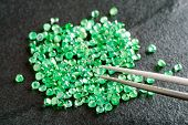 stock photo of emerald  - Pile of green round cut emeralds on black stone plate - JPG