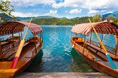 pic of pier a lake  - Traditional wooden boats on picture perfect lake Bled - JPG
