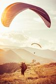 pic of hang-gliding  - Paragliding extreme Sport with mountains on background Healthy Lifestyle and Freedom concept Summer Vacations