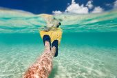 pic of leg-split  - Split above and underwater photo of woman legs with fins at shallow water on tropical beach - JPG