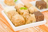 stock photo of baklava  - Baklava - Middle Eastern sweet pastry and nuts selection on an orange background.