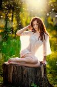 stock photo of redhead  - Young beautiful red hair woman wearing a transparent white blouse posing on a stump in a green forest - JPG