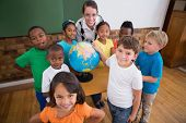 foto of classroom  - Cute pupils pointing to globe in classroom at the elementary school - JPG