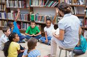 picture of classmates  - Cute pupils and teacher having class in library at the elementary school - JPG