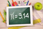 stock photo of math  - Composite image of digital tablet on students desk showing math equations - JPG