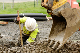 image of excavator  - Worker using a small tracked excavator to dig a hole to fix a water leak at a large commercial housing development in Oregon - JPG