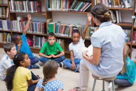 stock photo of librarian  - Cute pupils and teacher having class in library at the elementary school - JPG