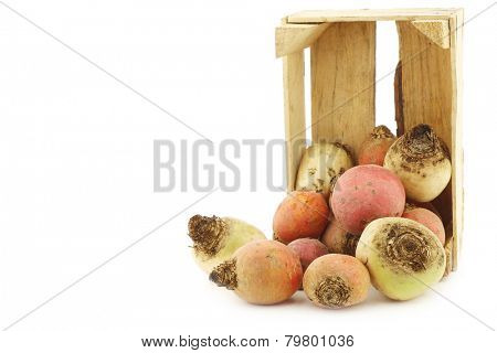 colorful mix of red,yellow and white beets in a wooden box on a white background