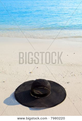 Black millinery from sun ays on sand before ocean