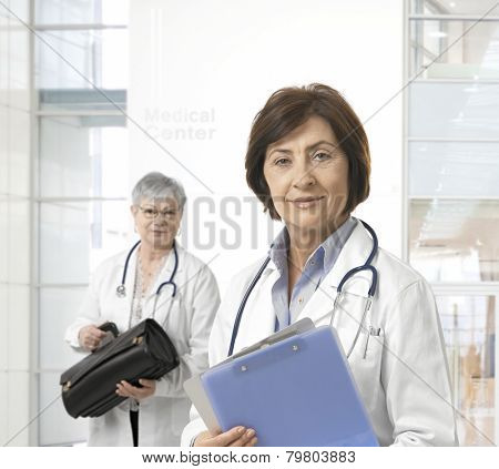 Portrait of mature female doctor, standing at hall of medical center.