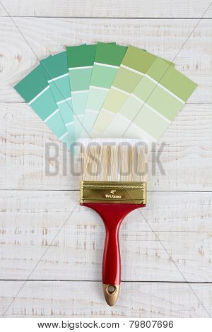 Overhead vertical shot of  a paint brush and shades of green color samples on a rustic white wooden surface.