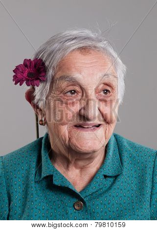 Elderly Woman Smiling With A Flower In Her Ear