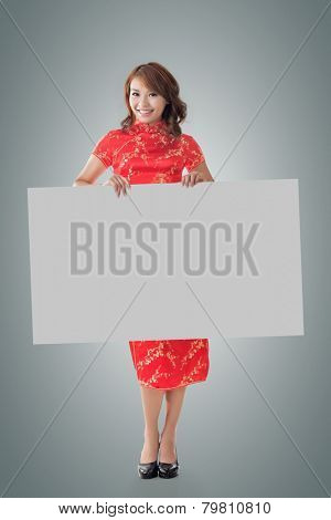 Attractive Chinese woman dress traditional cheongsam and hold blank board, full length portrait.