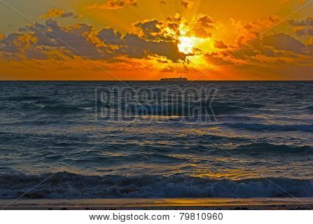 Dramatic sunrise with clouds over the ocean.