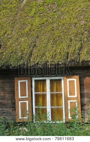 Old Wooden House With Wooden Shutters And Thatched Roof. Rural Buildings. Poland.