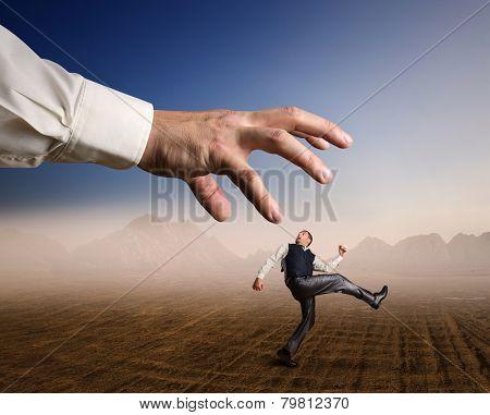 Businessman runs from a big arm