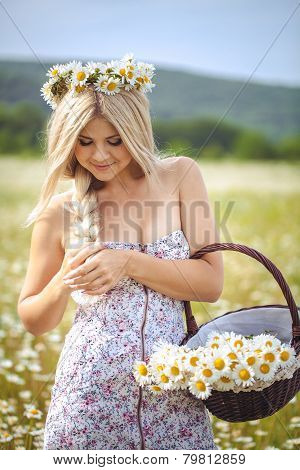 Portrait of beautiful young woman with flowers in the field