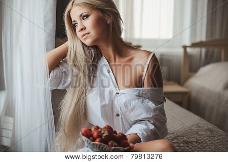 Young woman eating fresh strawberries for breakfast.