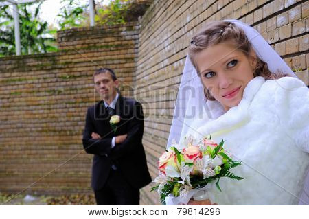 The Groom And The Bride Near A Wall