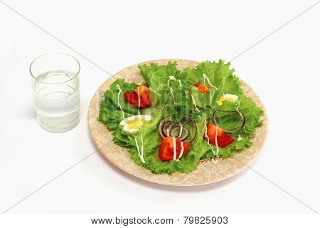 A vegetarian salad and a glass of water, isolated on white