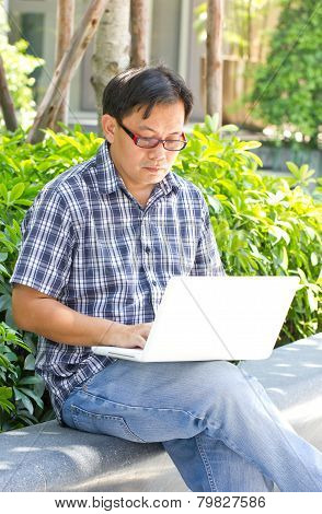 Asian Man Working With Laptop At Public Park.
