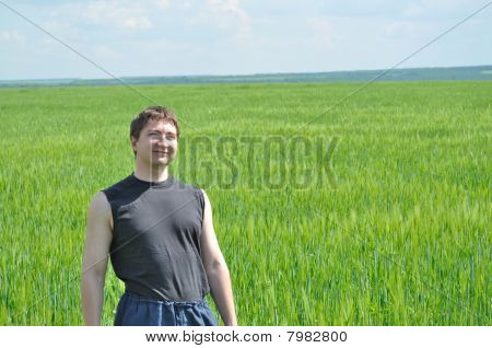 The field of green wheat, and a man on it