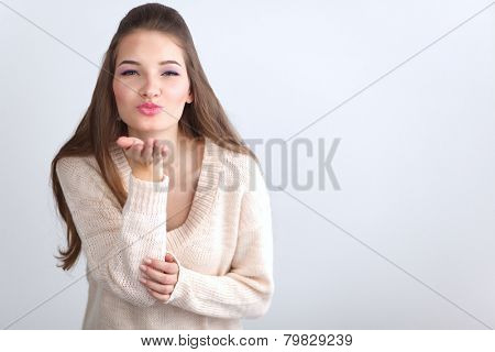 Young woman giving an air kiss, isolated on white