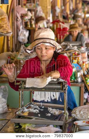 HOI AN, VIETNAM - MARCH 31: Unidentified woman making rice noodles on the Hoi An market, Vietnam on March 31, 2014.