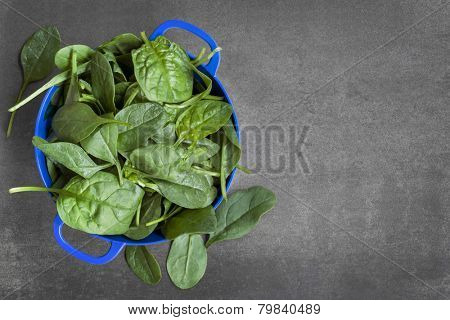 Spinach colander, over dark slate.