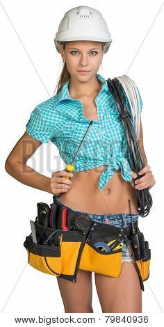 Serious electrician in helmet, shorts, shirt, tool belt with tools holding screwdriver and an electr