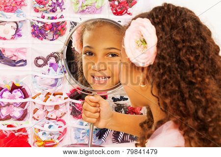 Beautiful small African girl reflects in mirror