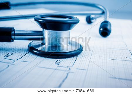 Stethoscope on cardiogram concept for heart care on the desk.blue toned images.