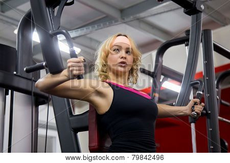 Girl Lifts Weights In Gym On A Butterfly Machine