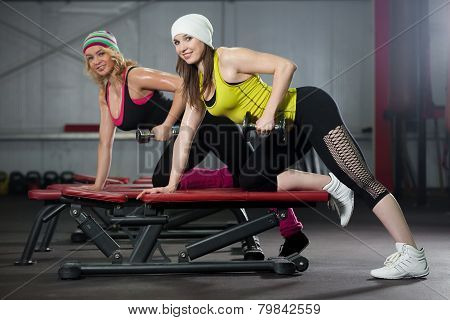 Two Girls Train In Gym With Dumbbells