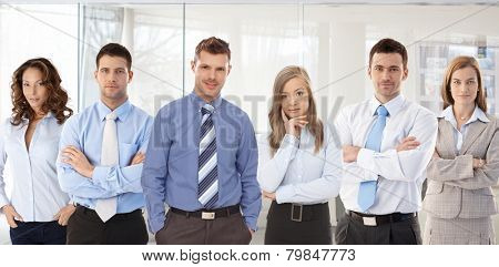 Team photo of successful young confident businesspeople standing at office.