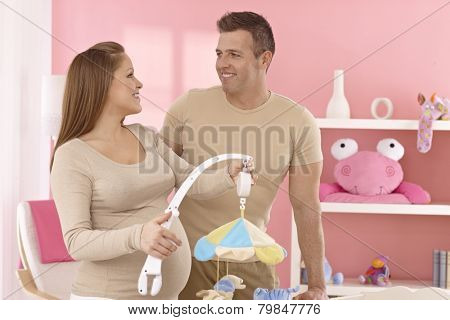 Happy young expecting couple in baby's room.