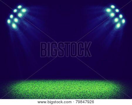 Spotlights illuminating area of grass court