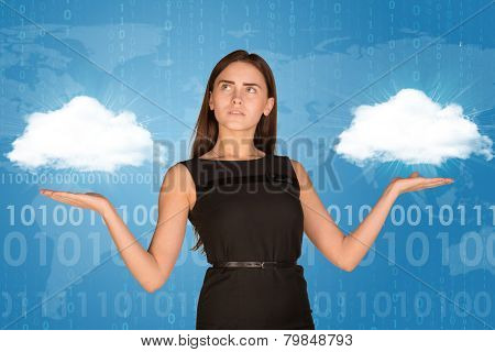 Businesswoman holding two white clouds, as if chosing