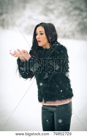 View of happy brunette girl playing with snow in winter landscape. Beautiful young female on winter