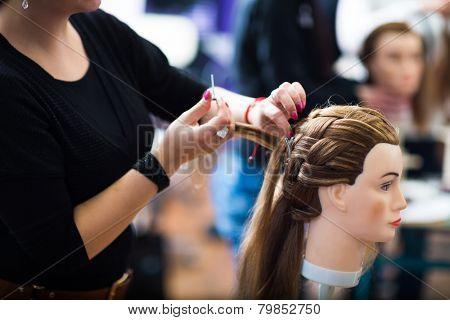 Pretty female hairdresser/haidressing apprentice/student training on an apprentice head