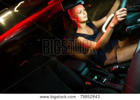 Driving a car at night - pretty, young woman driving her modern car at night, in a city (shallow DOF; color toned image)
