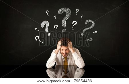 Depressed businessman sitting under question marks