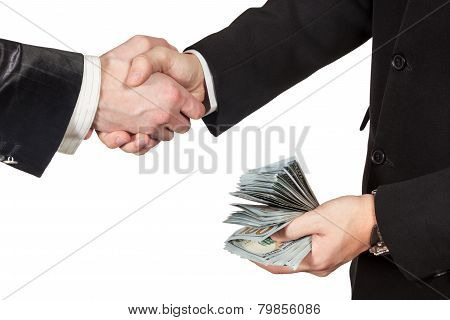 Handshake of two businessmen with money in hand